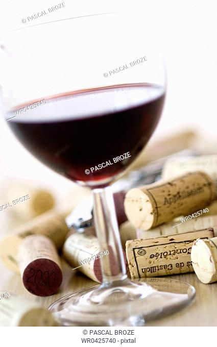 Close-up of a glass of red wine and corks