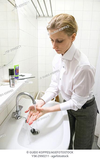 Tilburg, Netherlands. Gender Bender portrait of Johanna, washing her hands after doing her hair in front of her bathroom mirror