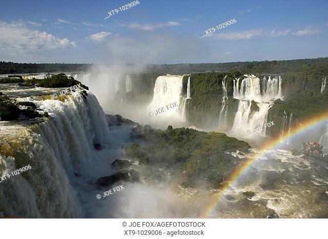 water flowing over iguazu falls with tourists and rainbow brazilian side iguacu national park, parana, brazil, south america