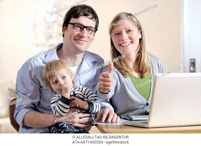 Happy family in front of a notebook