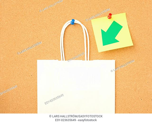 Paper shoppingbag with handles on message board in office. Concept of shopping reminder and retail business