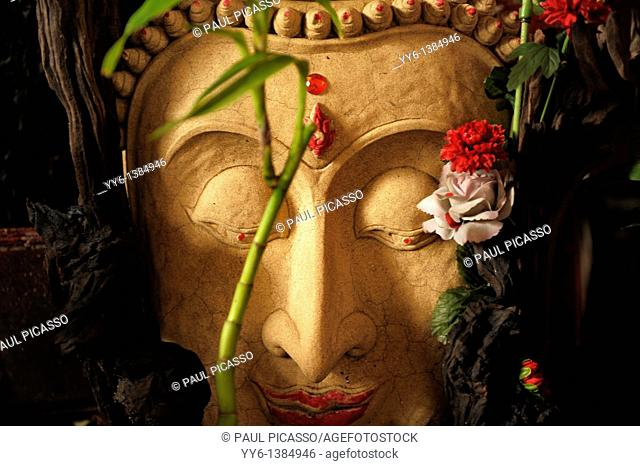 buddha stone image decorated with flowers , chinatown , bangkok, thailand