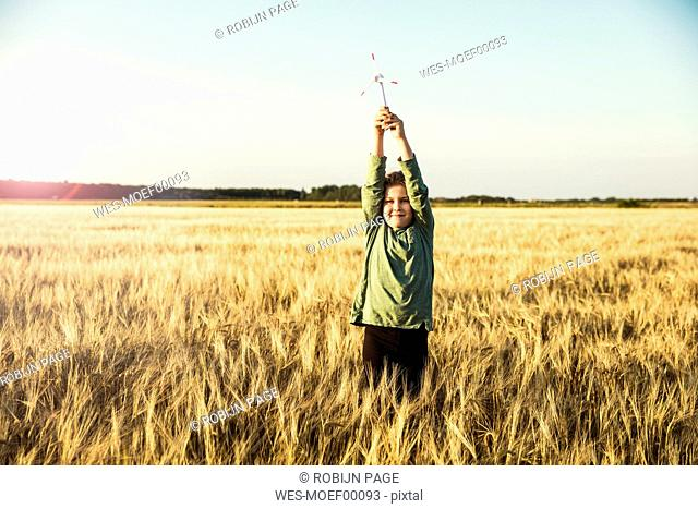 Girl standing in grain field holding miniature wind turbine