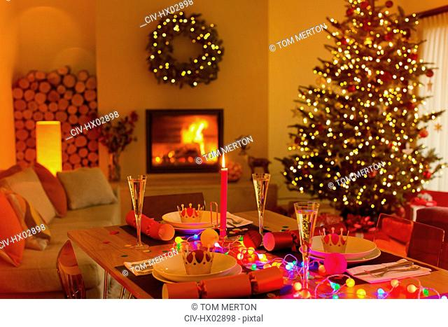 Ambient Christmas dinner table in living room with fireplace and Christmas tree