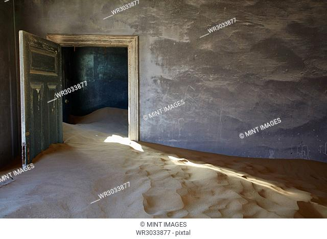 An abandoned building, an open door and drifts of sand encroaching into the room from the rest of the building. A ghost town