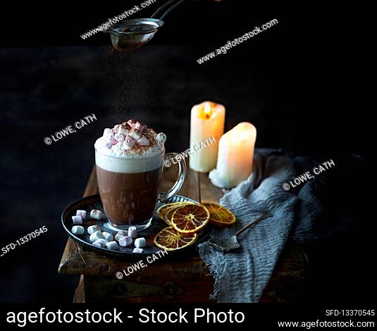 Hot chocolate with frothy milk and cocoa powder