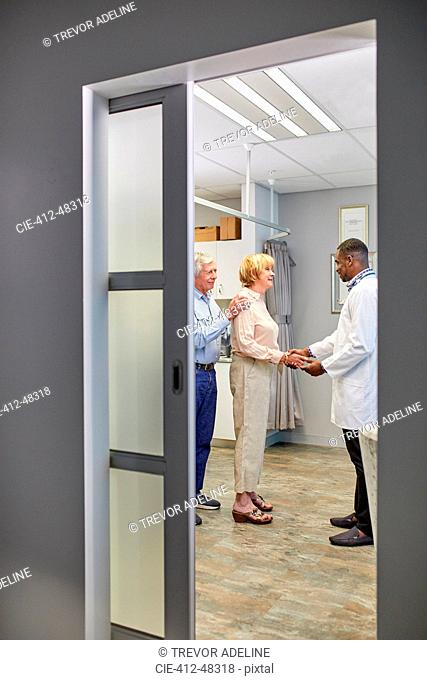 Doctor shaking hands with senior couple in clinic examination room
