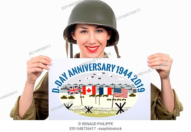 smiling young woman dressed in wwii military uniform with helmet showing signboard with d-day anniversary