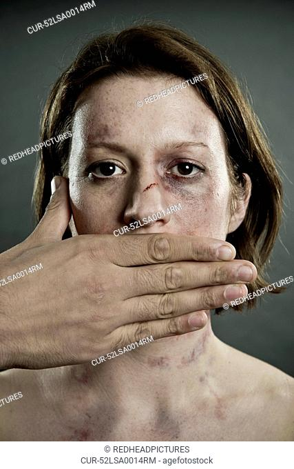 Woman with bruises and mouth covered