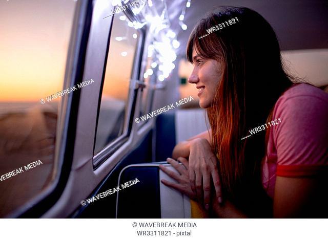 Woman looking through window of a camper van at beach