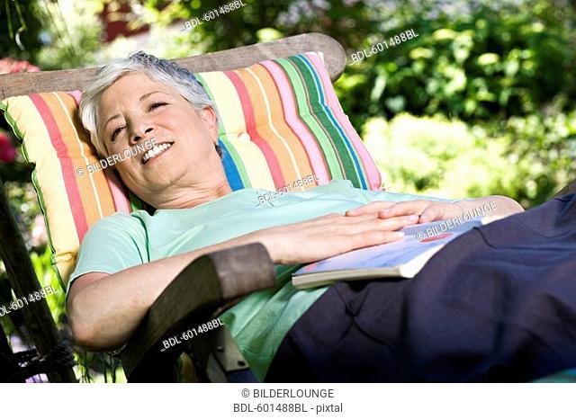 mature woman relaxing on deck chair in garden