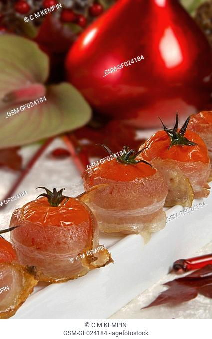 Baked cherry tree tomatoes wrapped up in bacon