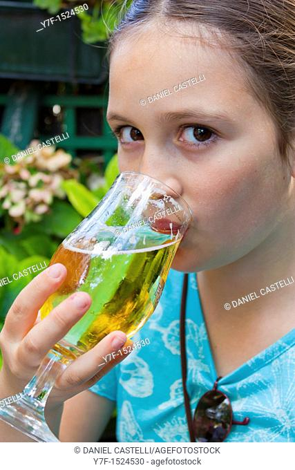 Brown eyed teenager drinking a glass of beer in a french café,Paris,France