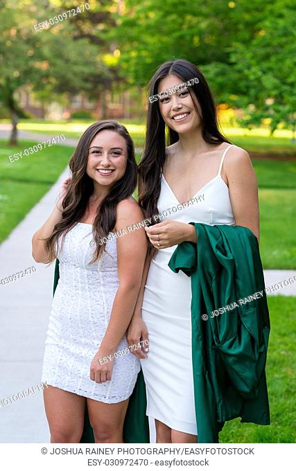 Two college girls and best friends walk on a sidewalk while holding their caps and gowns before graduation on a university campus during the Spring in Oregon