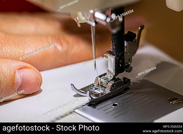 Sewing machine up close, on the foot and the needle. Making smocks for caregivers