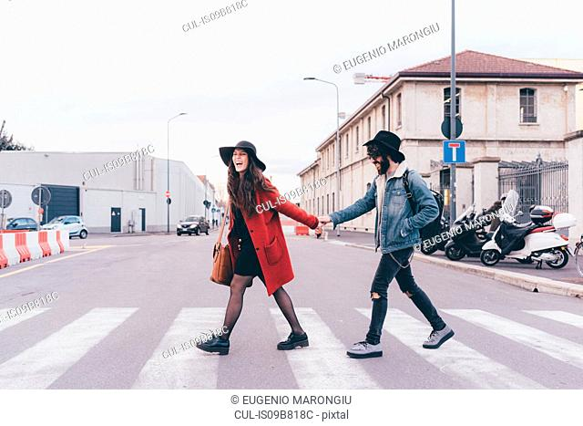 Young couple crossing road, holding hands, laughing