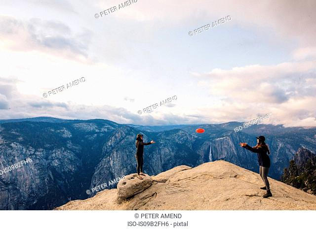 Young woman playing with flying disc at top of mountain overlooking Yosemite National Park, California, USA