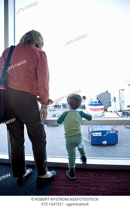 A grandmother and her grandson looking out of the window at an airplane parked at the gate, while they wait to board