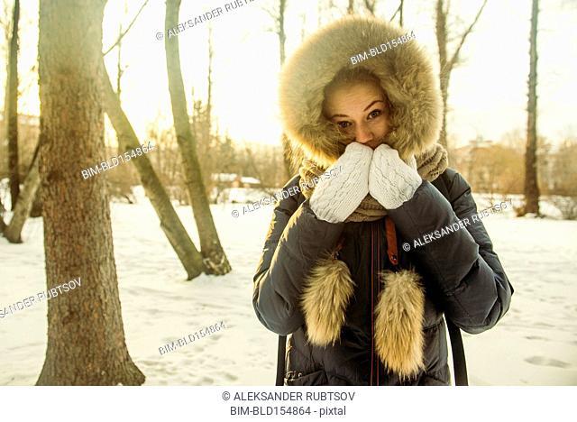 Caucasian woman wearing fur hood and coat in snowy field