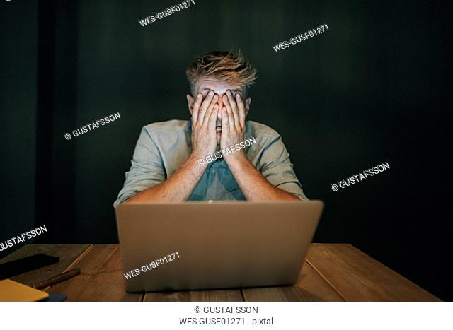 Tired man sitting in office, working late in his start-up company, covering eyes