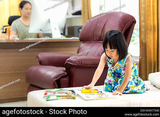 Asian girl child reading interactive book in living room at home as home schooling while her mom working at home because city lockdown because of covid-19...