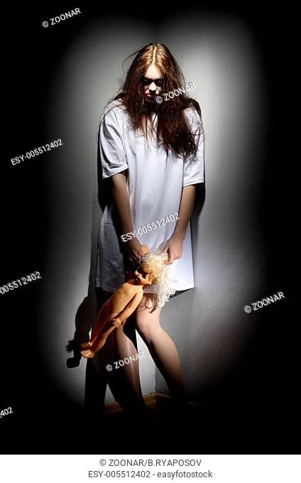 Zombie girl holding plastic doll