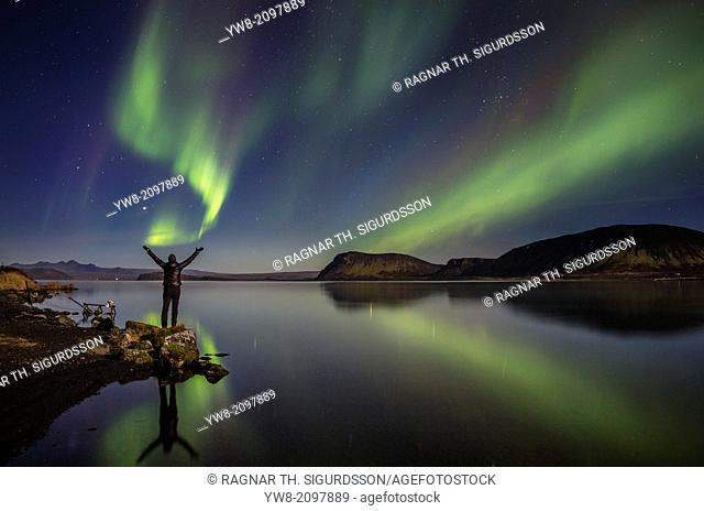 Woman enjoying the view of the Northern Lights, at Lake Thingvellir, Iceland. Thingvellir National Park is a UNESCO World Heritage Site