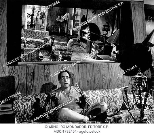 A man is seated on a sofa with his legs crossed, he is on the telephone and smokes a narghile in a scene from the movie Aandhiyan