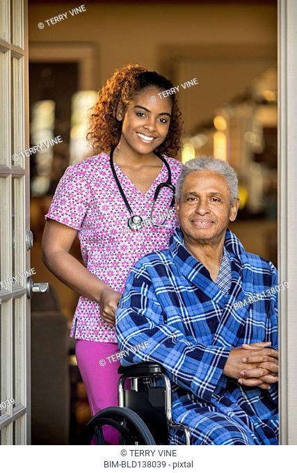 African American nurse wheeling Senior patient outdoors