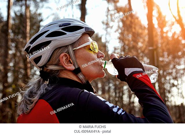 Side view of woman wearing cycling helmet and sunglasses drinking water from plastic bottle