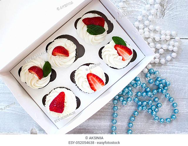 Chocolate cupcakes with white creme and strawberry on top in the white box
