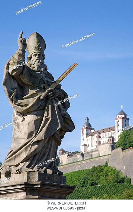 Germany, Bavaria, Franconia, Stone-Carved Statue of a Saint and the Marienberg Fortress