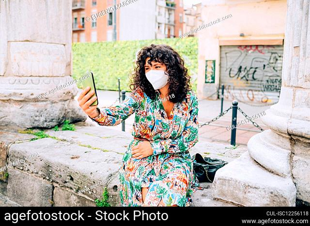 Young woman wearing face mask during Corona virus, sitting outdoors, taking selfie