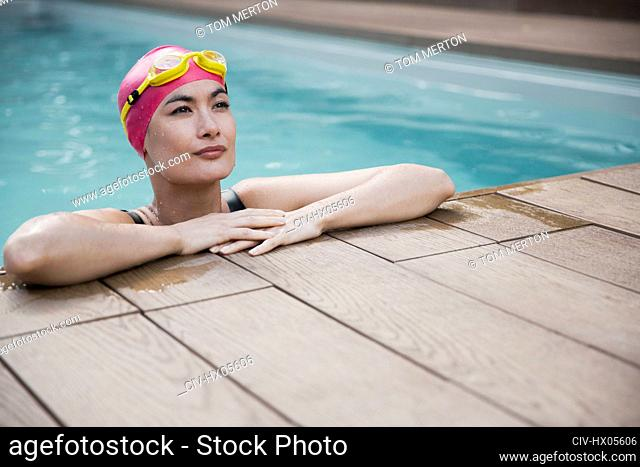 Confident woman in swimming cap and goggles leaning on edge of swimming pool