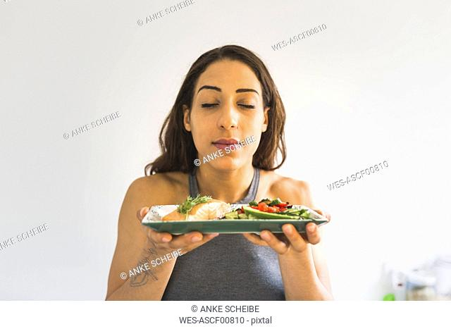 Woman holding plate with vegetables and salmon