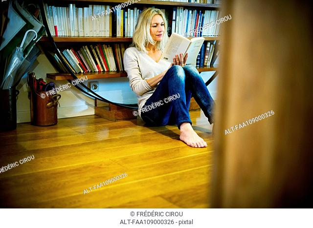 Woman sitting on floor reading book at home