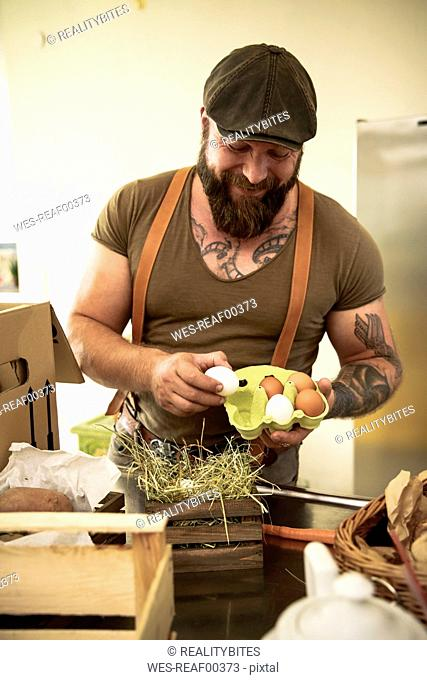 Mature man with delivery service checking eggs, before packing them in cardboard boxes