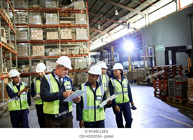 Manager and workers talking in distribution warehouse