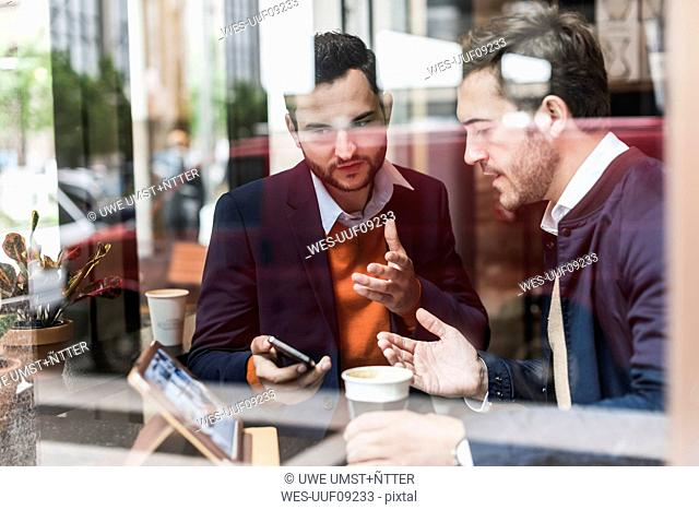 USA, New York City, Businessmen meeting in coffee shop, using mobile devices