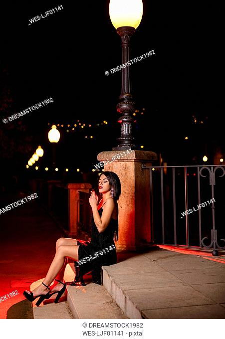 Young woman wearing black evening dress sitting on stairs at night smoking cigarette