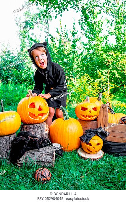 Halloween. Child dressed in black with jack-o-lantern in hand, trick or treat. Scaring little girl with pumpkin in the wood, outdoors