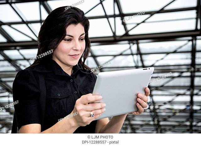 Mature businesswoman using her touch screen pad in the atrium of an office building; Edmonton, Alberta, Canada