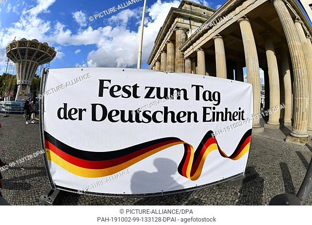 "02 October 2019, Berlin: A banner with the inscription """"Fest zum Tag der Deutschen Einheit"""" can be seen in front of the Brandenburg Gate. On 03.10"