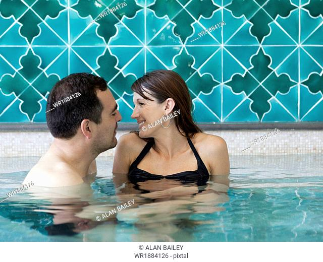 Italy, Amalfi Coast, Ravello, Mature couple laughing in swimming pool