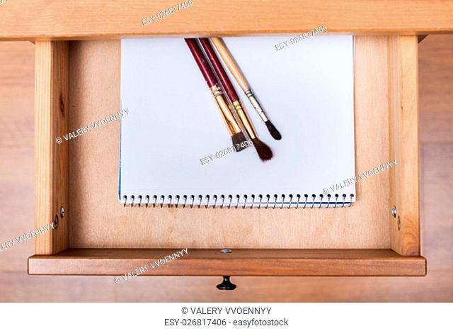 above view of paint brushes on drawing album in open drawer of nightstand