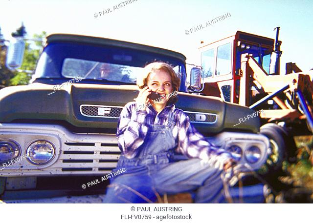 Young woman sitting on old pick-up truck talking on a cell phone