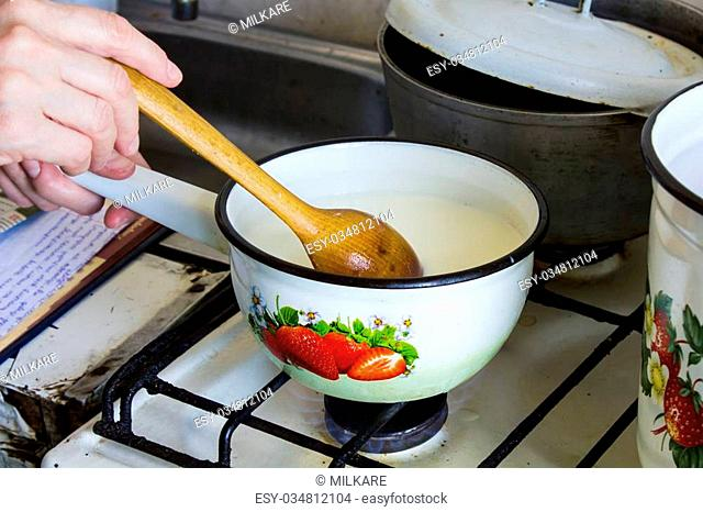 Female hands warmed milk stirring with a wooden spoon in a pot on the stove