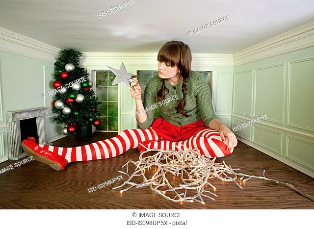 Young woman in small room with christmas decorations