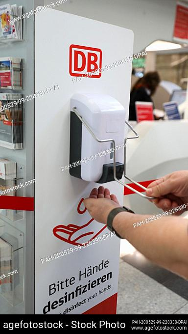 27 May 2020, Saxony, Leipzig: A traveller disinfects his hands at Leipzig central station. With more disinfectant hand dispensers