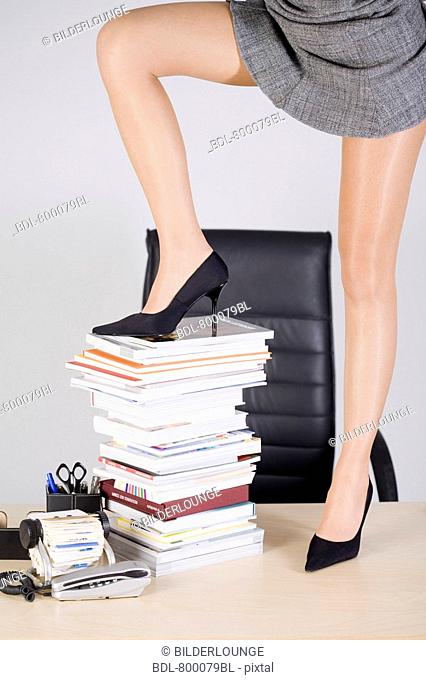 detail of young businessman wearing high heel shoes putting one foot on pile of books